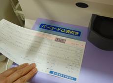 自動支払機に請求書のバーコードをかざす